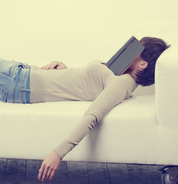 Woman lying with book next to Screw it! wine